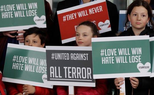 Niños muestran carteles con mensajes de unidad.
