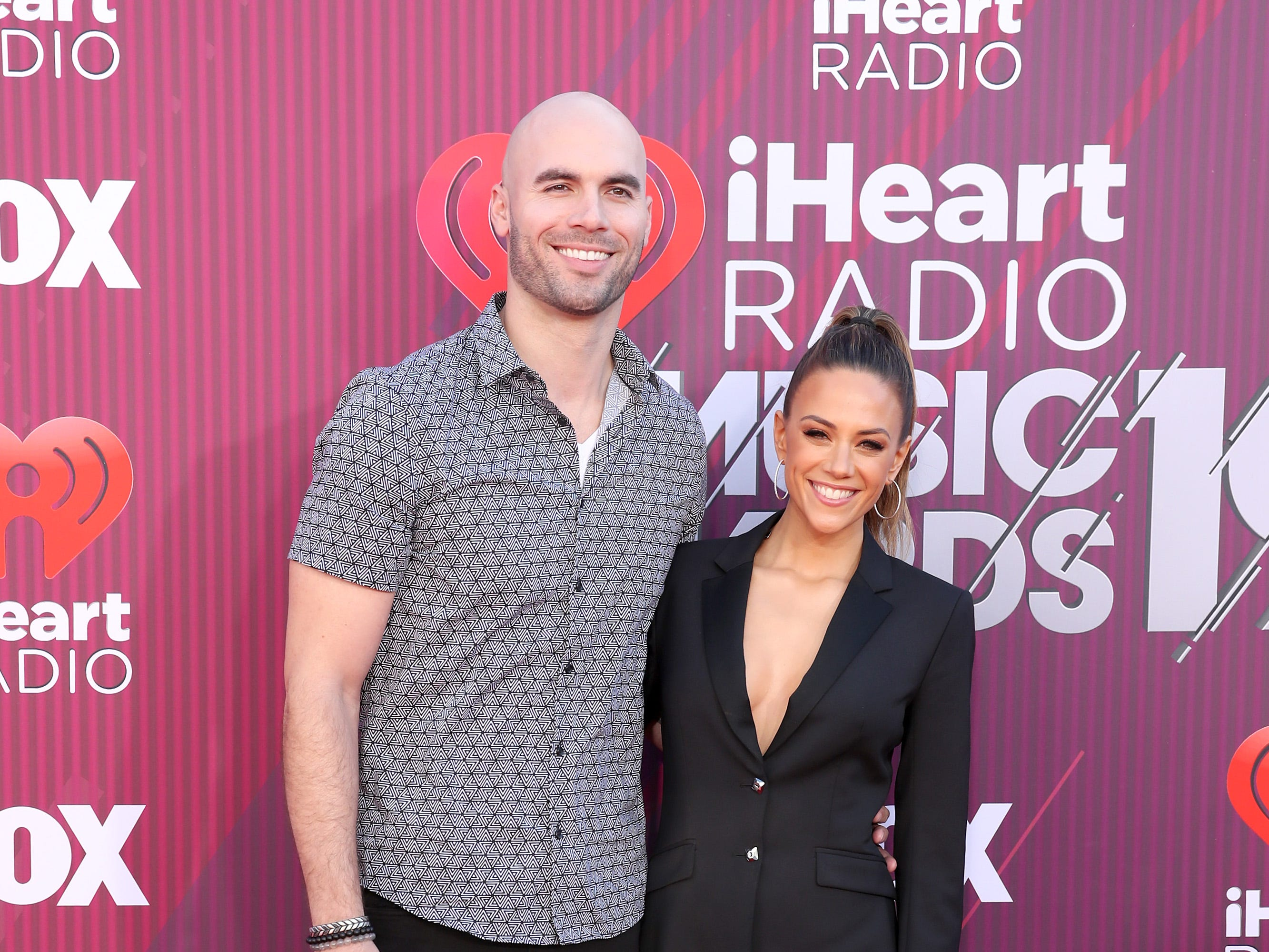 Mike Caussin y Jana Kramer a su llegada a los premios iHeart Radio Music Awards en 2019 el 14 de marzo de 2019 en Los Angeles, California.