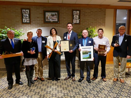 From left: Mayor Ken Harsanje (accepting on behalf of Gordon Lumber), Jen and Eric Booker (Boardwalk Family of Restaurants), Rebekah and Tony Zimmerman (Wine Flight), Administrator Kevin Gladden (Village of Genoa), Ron Lajti (Ottawa County Engineer), and Bob Babjack (The Chipmatic Company).