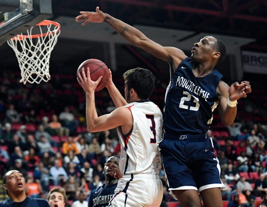 Poughkeepsie's Jaquan Pearson, right, defends against Manhasset's Joseph LoCurto during a Class A semifinal at the NYSPHSAA Boys Basketball Championships in Binghamton, N.Y., Friday, March 15, 2019. Poughkeepsie advanced to the Class A final with a 74-63 win over Manhasset-VIII.