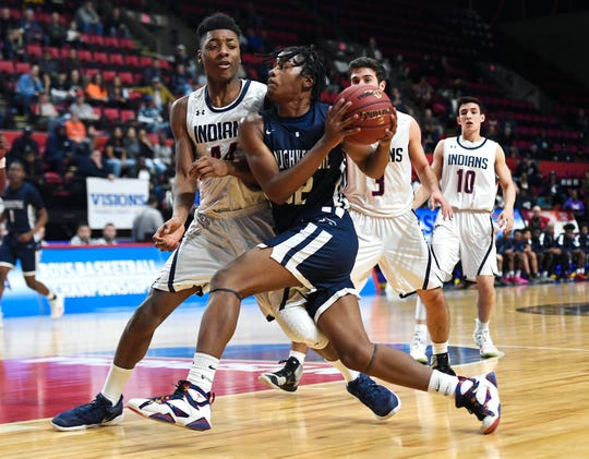 Poughkeepsie's Niyal Goins, right, is defended by Manhasset's Ahmad Crowell during a Class A semifinal at the NYSPHSAA Boys Basketball Championships in Binghamton, N.Y., Friday, March 15, 2019. Poughkeepsie advanced to the Class A final with a 74-63 win over Manhasset-VIII.
