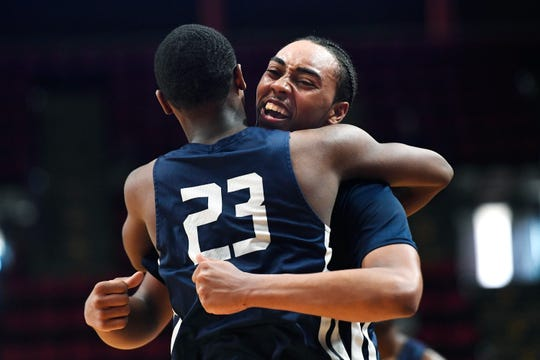 Poughkeepsie's Davontrey Thomas, facing, celebrates with Jaquan Pearson after winning a Class A semifinal against Manhasset at the NYSPHSAA Boys Basketball Championships in Binghamton, N.Y., Friday, March 15, 2019. Poughkeepsie advanced to the Class A final with a 74-63 win over Manhasset-VIII.