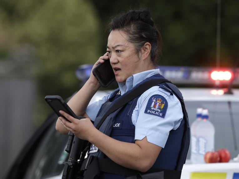 A police officer talks on her phone as a roadblock near a mass shooting at a mosque in Linwood, Christchurch, New Zealand, Friday, March 15, 2019. Multiple people were killed during shootings at two mosques full of people attending Friday prayers. (AP Photo/Mark Baker)