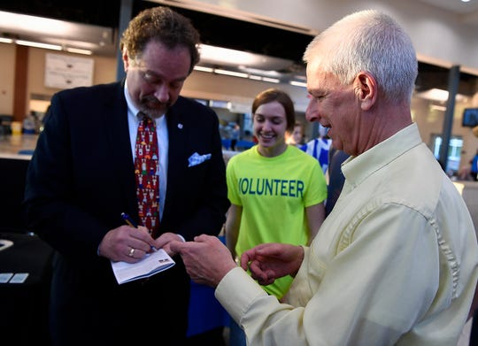 Spring Grove School District's soon to be outgoing superintendent Dr. David Renaut, right, gets his program signed by incoming superintendent George Ioannidis during the high school's third annual Diversity Festival, Thursday, March 13, 2019. Dr. Renaut is retiring in July.