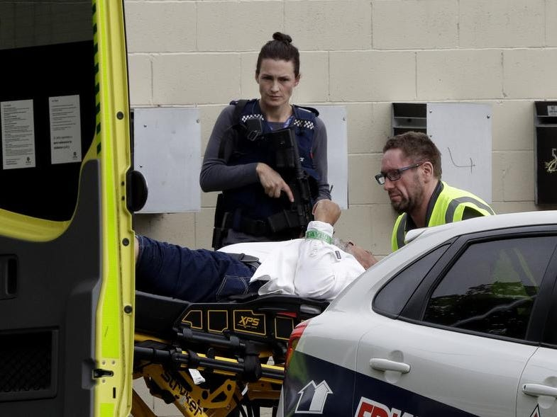 An armed police officer watches as a man is taken by ambulance staff from a mosque in central Christchurch, New Zealand, Friday, March 15, 2019.   Multiple people were killed in mass shootings at two mosques full of people attending Friday prayers, as New Zealand police warned people to stay indoors as they tried to determine if more than one gunman was involved. (AP Photo/Mark Baker)