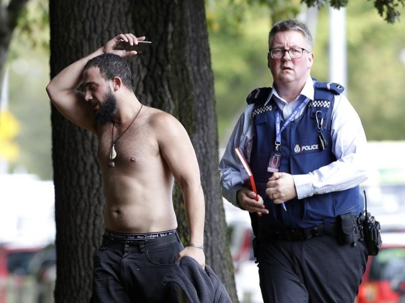 A police officer escorts a man away from a mosque in central Christchurch, New Zealand, Friday, March 15, 2019. Multiple people were killed in mass shootings at two mosques full of people attending Friday prayers, as New Zealand police warned people to stay indoors as they tried to determine if more than one gunman was involved. (AP Photo/Mark Baker)