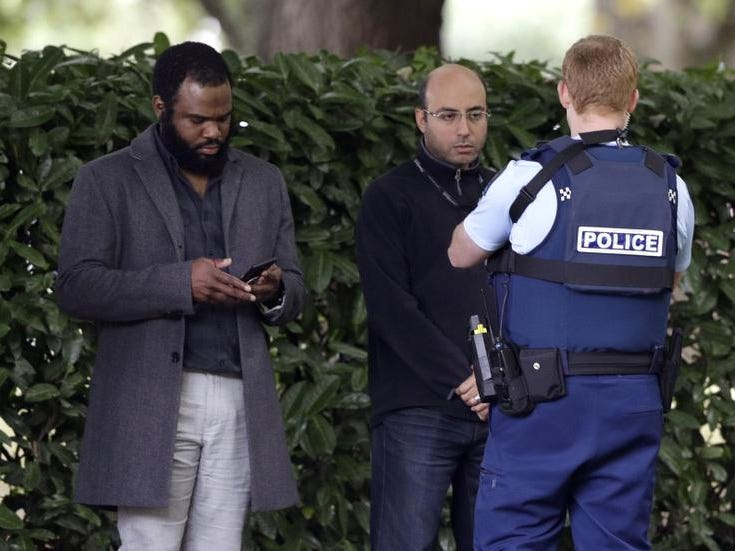 A police officer photographs witnesses near a mosque in central Christchurch, New Zealand, Friday, March 15, 2019. Multiple people were killed in mass shootings at two mosques full of people attending Friday prayers, as New Zealand police warned people to stay indoors as they tried to determine if more than one gunman was involved.(AP Photo/Mark Baker)