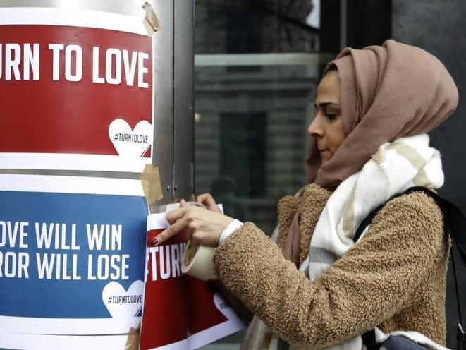 "A demonstrator hangs banners from multi-faith group 'Turn to Love' during a vigil at New Zealand House in London, Friday, March 15, 2019. Multiple people were killed in mass shootings at two mosques full of worshippers attending Friday prayers on what the prime minister called ""one of New Zealand's darkest days,"" as authorities detained four people and defused explosive devices in what appeared to be a carefully planned attack. (AP Photo/Kirsty Wigglesworth)"