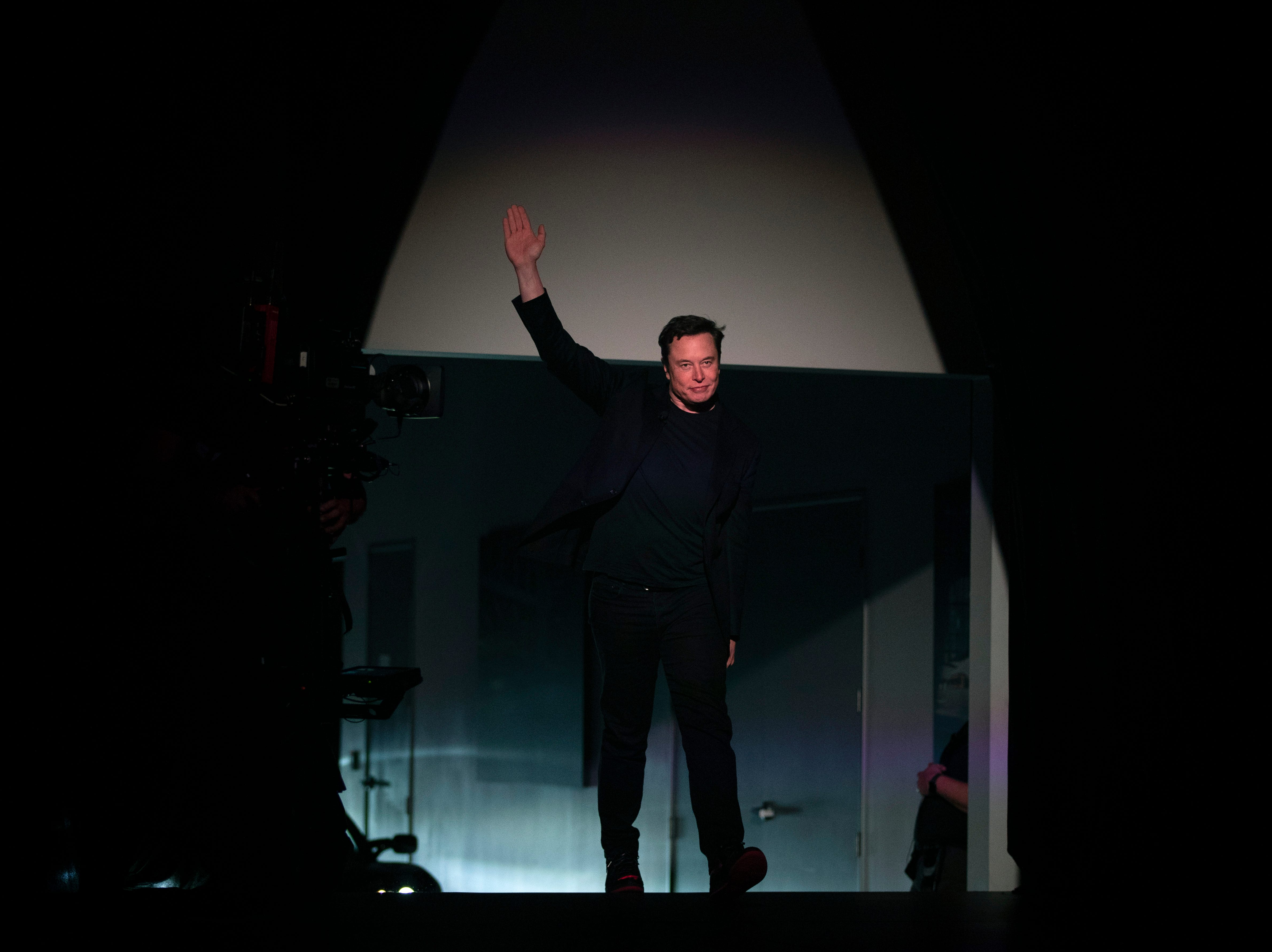 Tesla CEO Elon Musk waves as he walks onto the stage to introduce the Model Y at the company's design studio Thursday, March 14, 2019, in Hawthorne, Calif. The Model Y may be Tesla's most important product yet as it attempts to expand into the mainstream and generate enough cash to repay massive debts that threaten to topple the Palo Alto, California, company. (AP Photo/Jae C. Hong)
