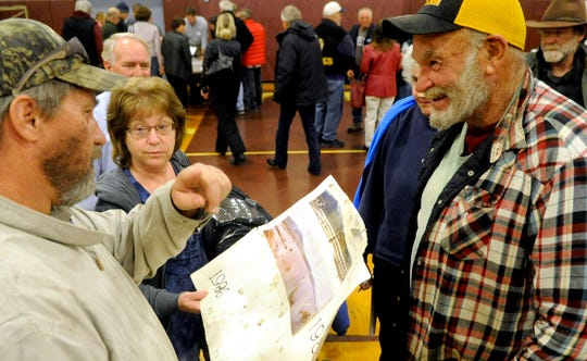 Tom Minor (left) shows old photos of flooding in Dayton.