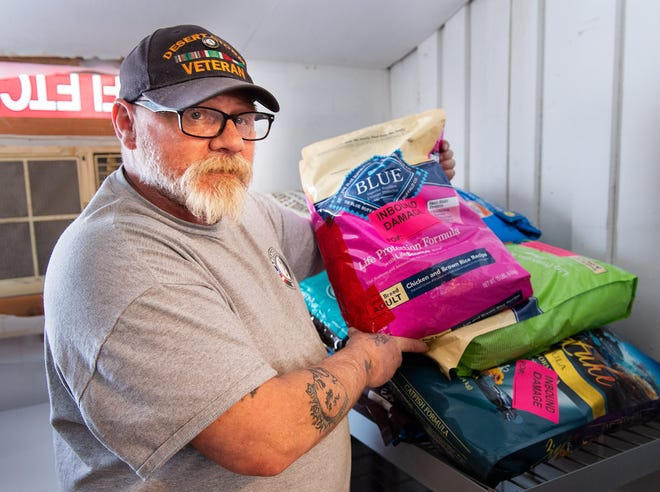 Ron Hoard, AmeriCorps Community Capacity Worker at the Yerington Food Pantry, shows dog food donated to YAPS by Chewy.