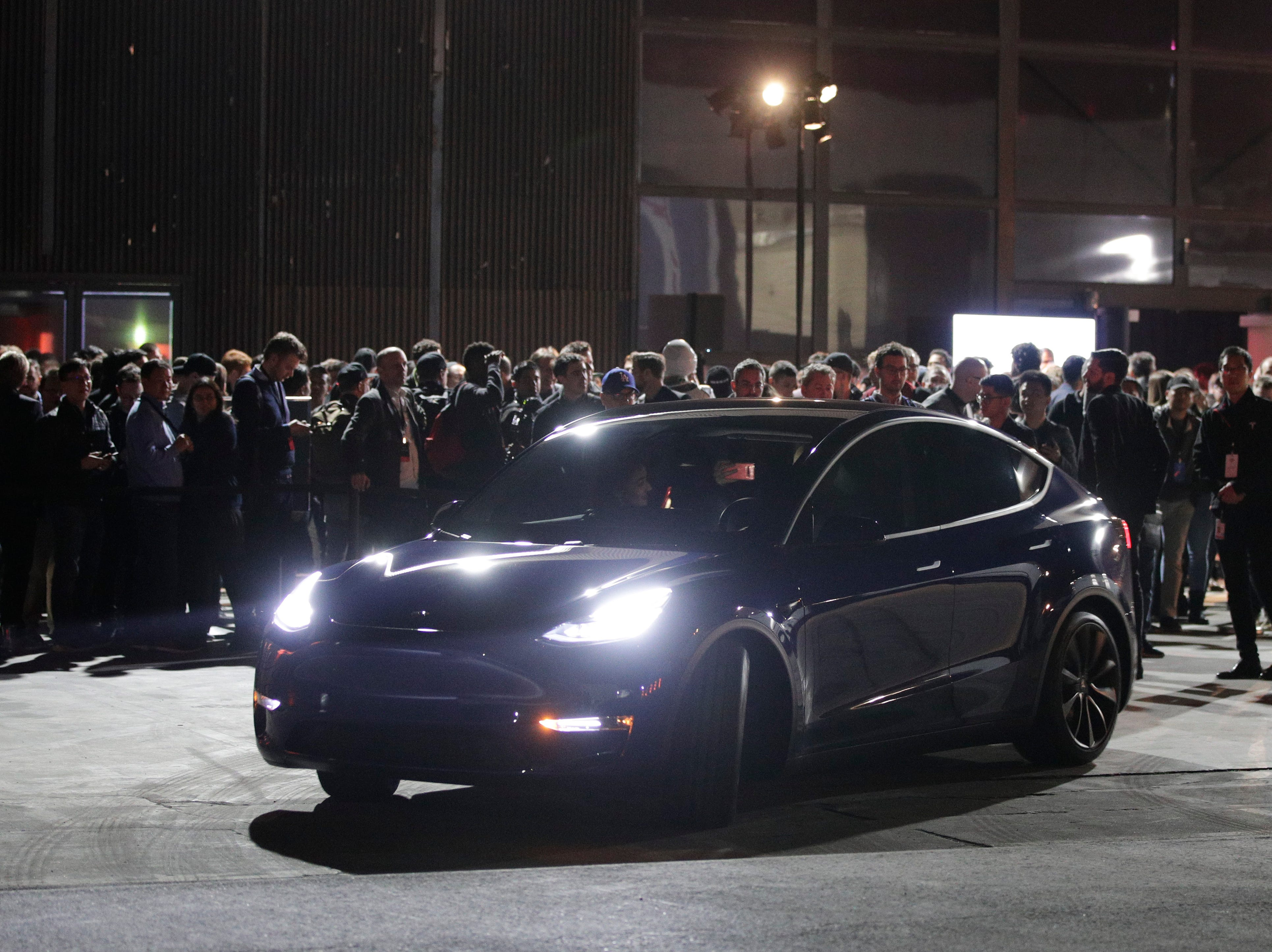 People wait outside Tesla's design studio for a test drive of the Model Y, Thursday, March 14, 2019, in Hawthorne, Calif. The Model Y may be Tesla's most important product yet as it attempts to expand into the mainstream and generate enough cash to repay massive debts that threaten to topple the Palo Alto, Calif., company. (AP Photo/Jae C. Hong)
