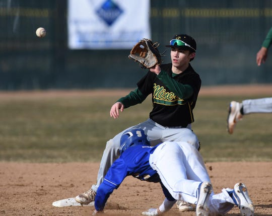 Bishop Manogue's Calvin Bailey looks to make the catch as Reed's Trae DeLeon slides into second base during Thursday's game at Reed. Manogue won, 7-1.