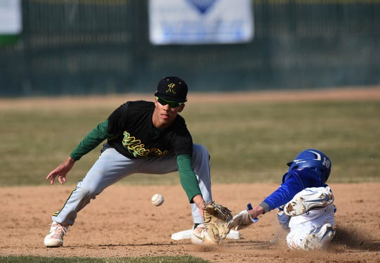 Bishop Manogue's Josh Rolling looks to tag Reed's Jordan Oliver at second base during Thursday's game. Manogue won, 7-1.