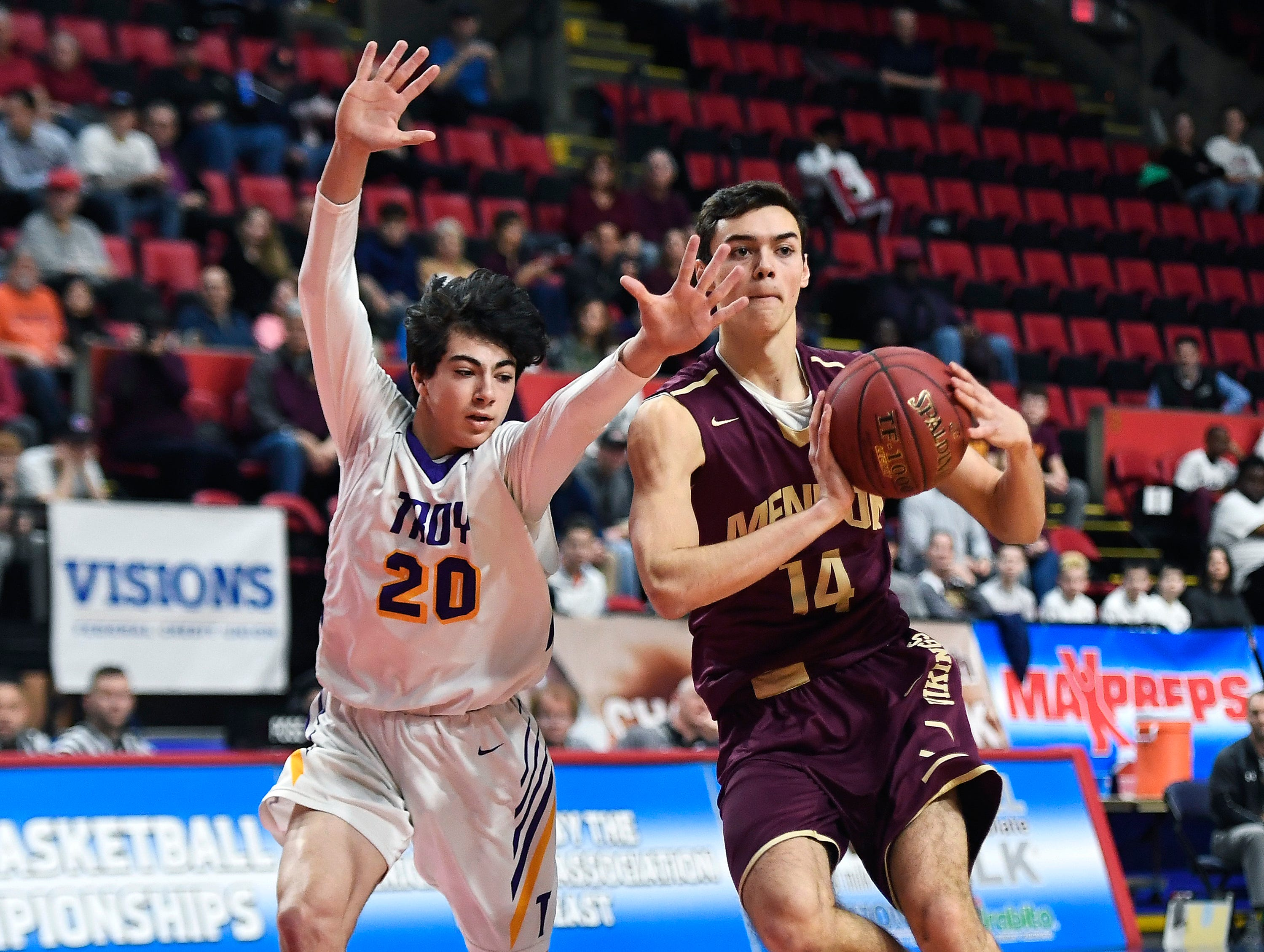 Pittsford Mendon's Dan Cook, right, passes the ball while defended by Troy's Alex Wolfe during a Class A semifinal at the NYSPHSAA Boys Basketball Championships.