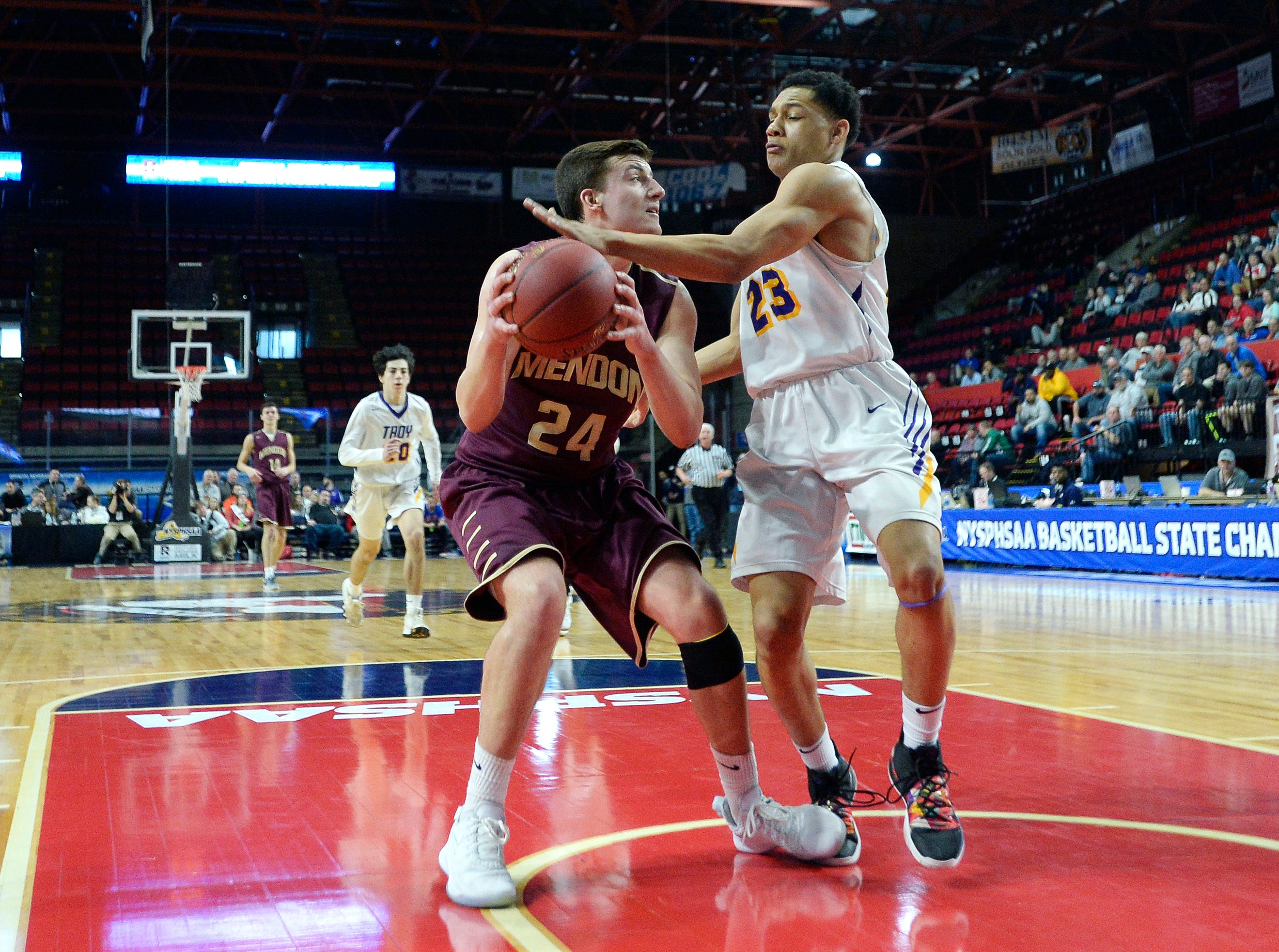 Pittsford Mendon's Nate Strauf, left, is defended by Troy's Latyce Faison during a Class A semifinal at the NYSPHSAA Boys Basketball Championships.