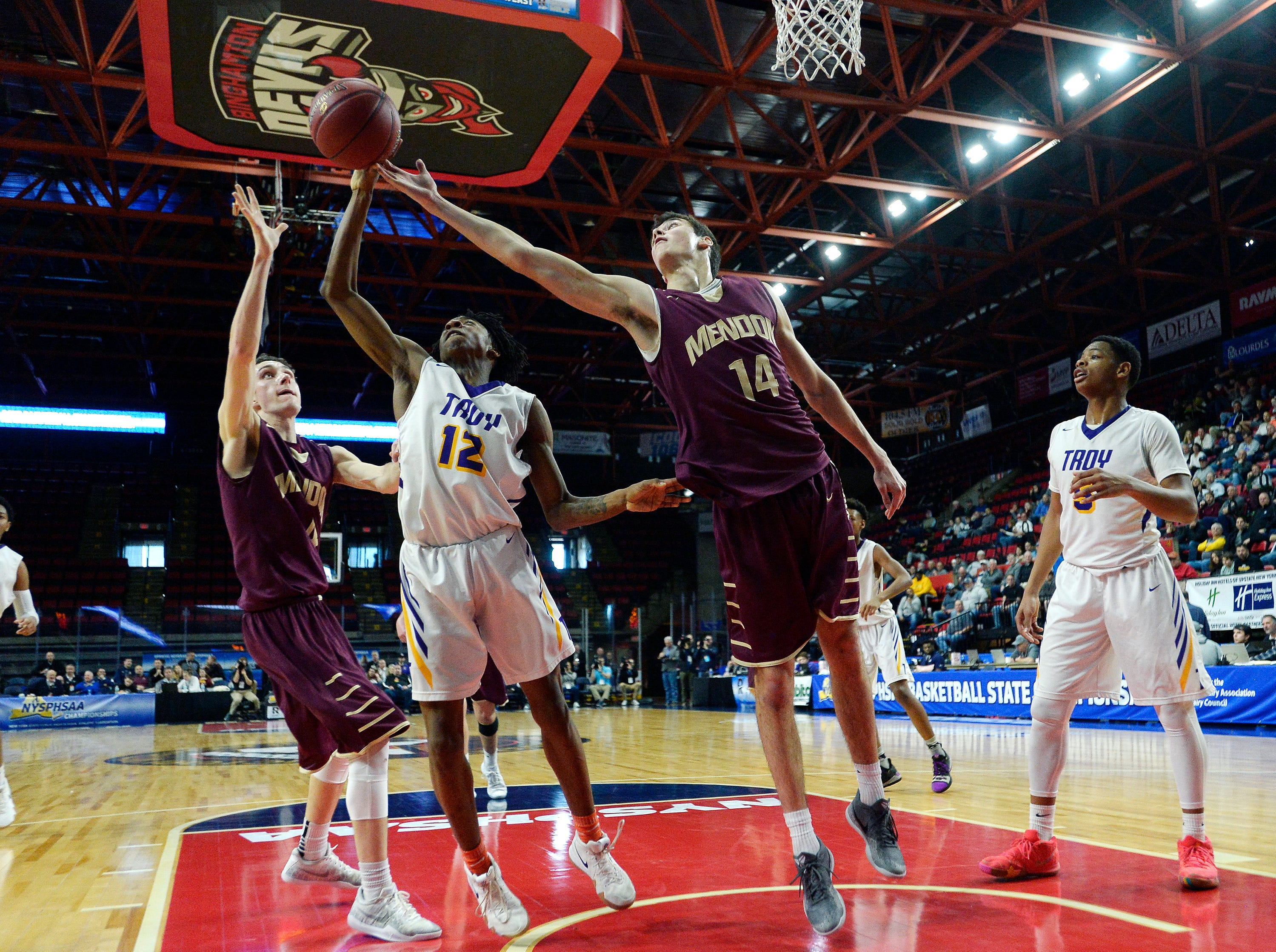 Pittsford Mendon's Dan Cook, right, and Connor Krapf, left, challenge Troy's Jay-Quan Moore for a rebound during a Class A semifinal.