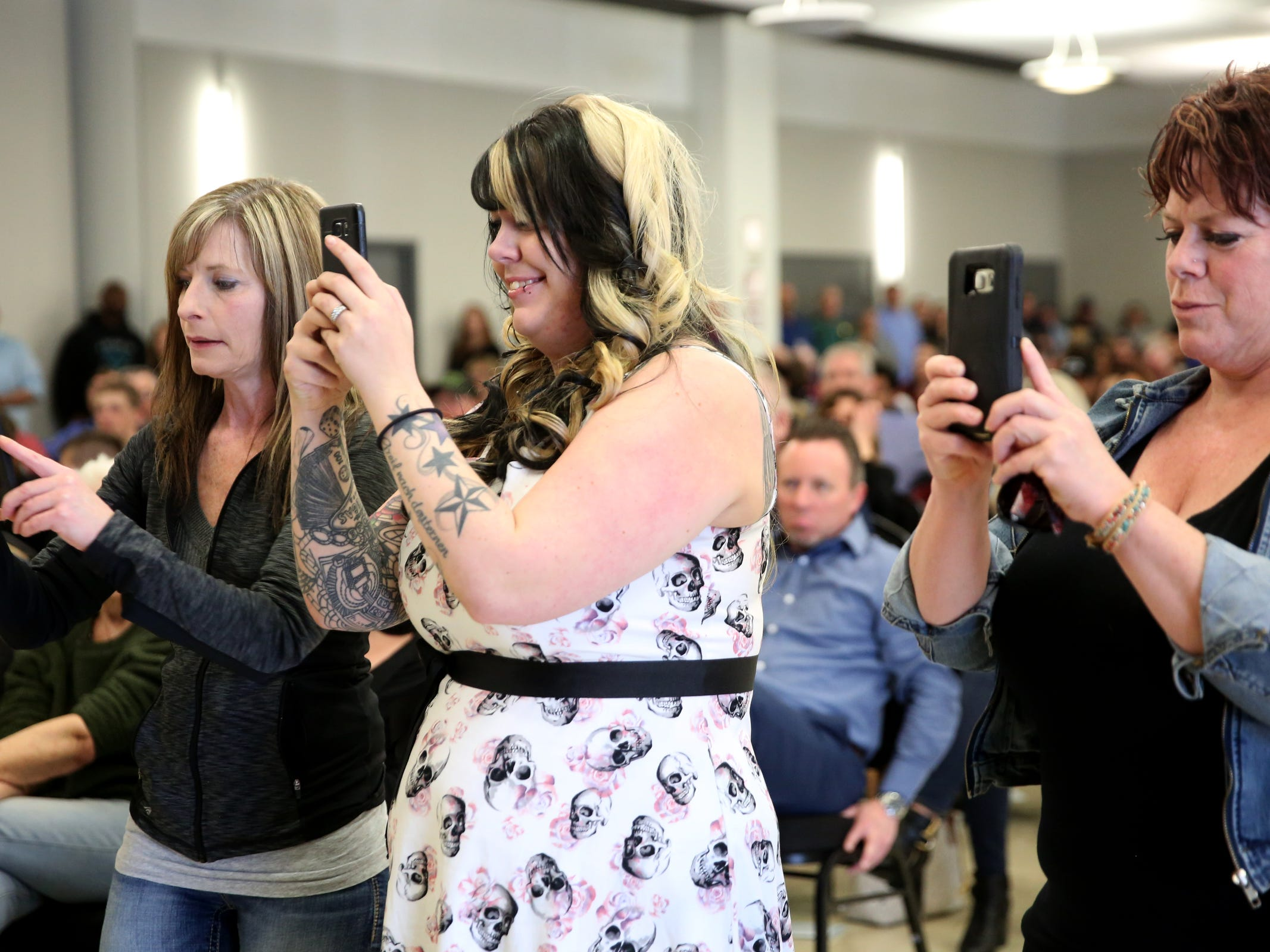Victoria Delano, from left, of Salem, Lisa Bush, of Salem, and Catherine Underwood-Bush, of Independence, take photos of Douglas Bush, a new Marion County Sheriff's Deputy, during a Basic Police Class graduation ceremony at the Department of Public Safety Standards and Training in Salem on March 15, 2019.