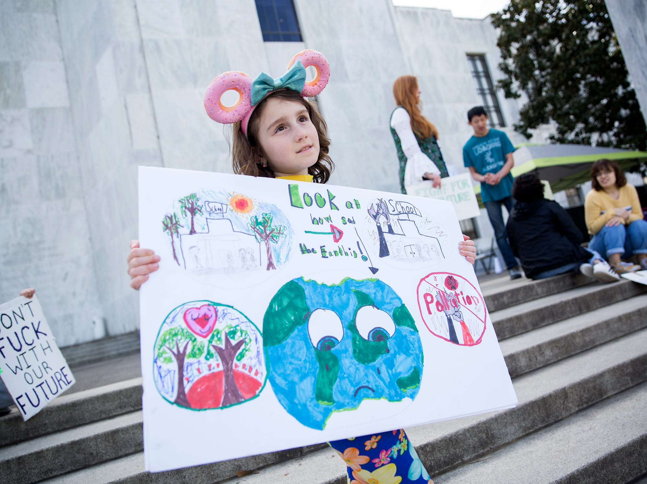 Amaya Woolley, 8, holds a sign during a student rally for climate change, in support of the Global Climate Strike and National Youth Climate Strike, at the Oregon State Capitol Building on March 15, 2019.