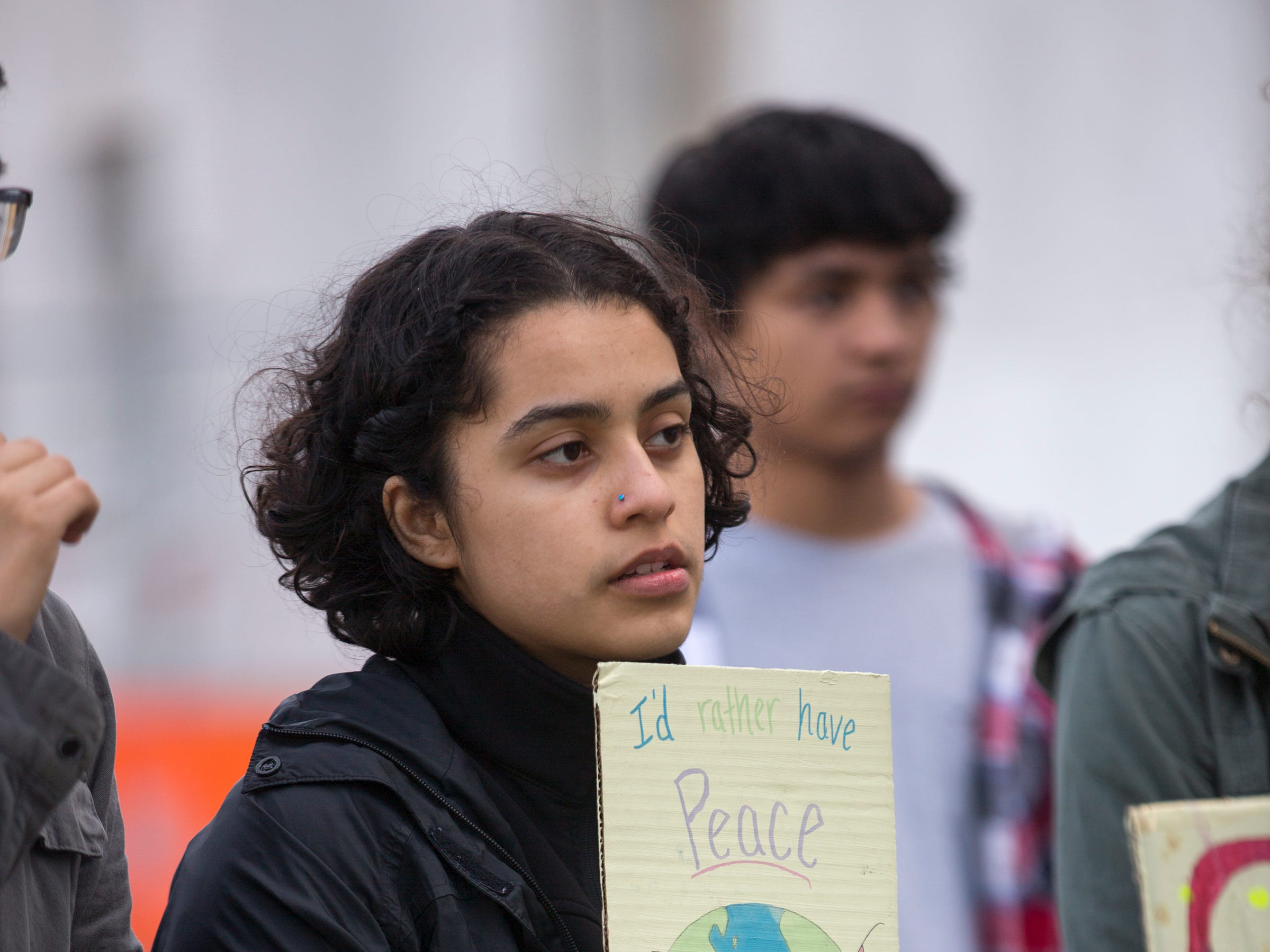 Diana Castaneda, a South Salem High School Senior, holds a sign and listens to students speak during a student rally for climate change, in support of the Global Climate Strike and National Youth Climate Strike, at the Oregon State Capitol Building on March 15, 2019.
