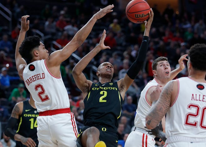 Oregon's Louis King, center, tries to shoot over Utah's Sedrick Barefield, left, during the second half of an NCAA college basketball game in the quarterfinals of the Pac-12 men's tournament Thursday, March 14, 2019, in Las Vegas.