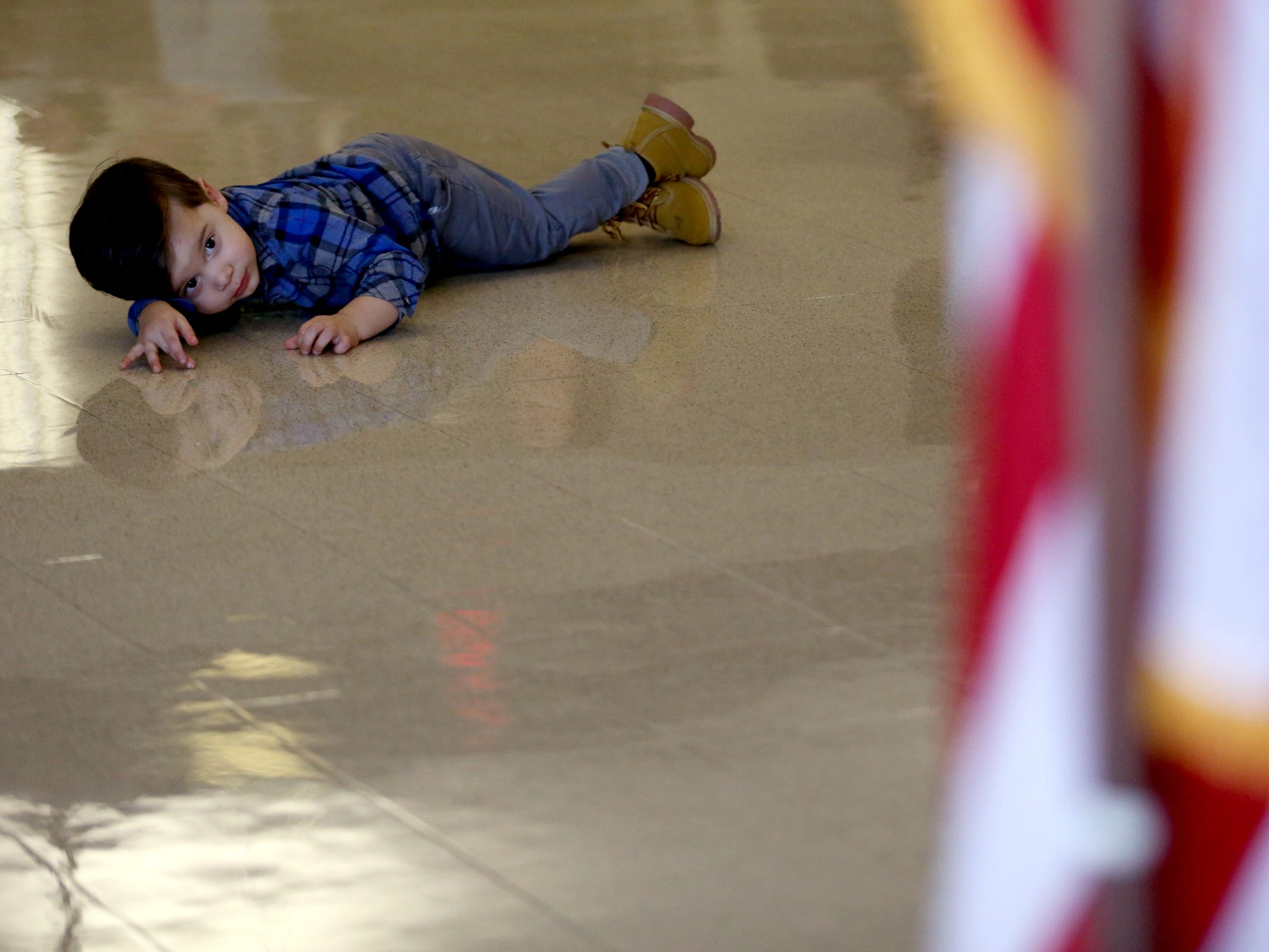 Troy Bell, 2, of Aumsville, lies on the floor as his mother is part of the newest Basic Police Class graduation ceremony at the Department of Public Safety Standards and Training in Salem on March 15, 2019.