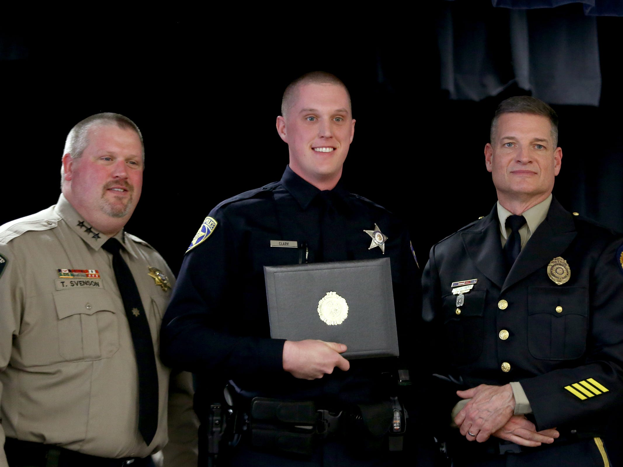 Joshua Clark, center, a new Salem Police officer, accepts his graduation certificate during a Basic Police Class graduation ceremony at the Department of Public Safety Standards and Training in Salem on March 15, 2019.