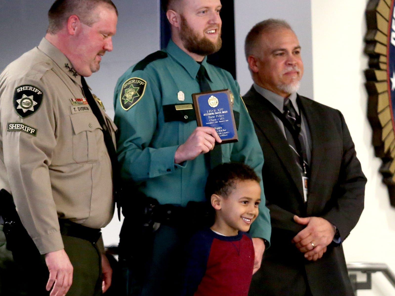 Jayden Ritchie, 5, of Tigard, stands on stage for a photo with his dad, Travis Ritchie, a new Multnomah County Sheriff's Deputy, during a Basic Police Class graduation ceremony at the Department of Public Safety Standards and Training in Salem on March 15, 2019.