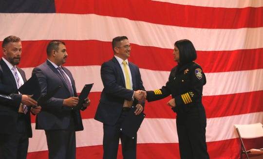 Salinas Police Chief Adele Fresé shakes hands with Det. Gabriel Gonzalez as Det. Ruben Sanchez and Sgt. Christopher Lane look on March 14, 2019, at the Salinas Police Department's 2018 awards ceremony.