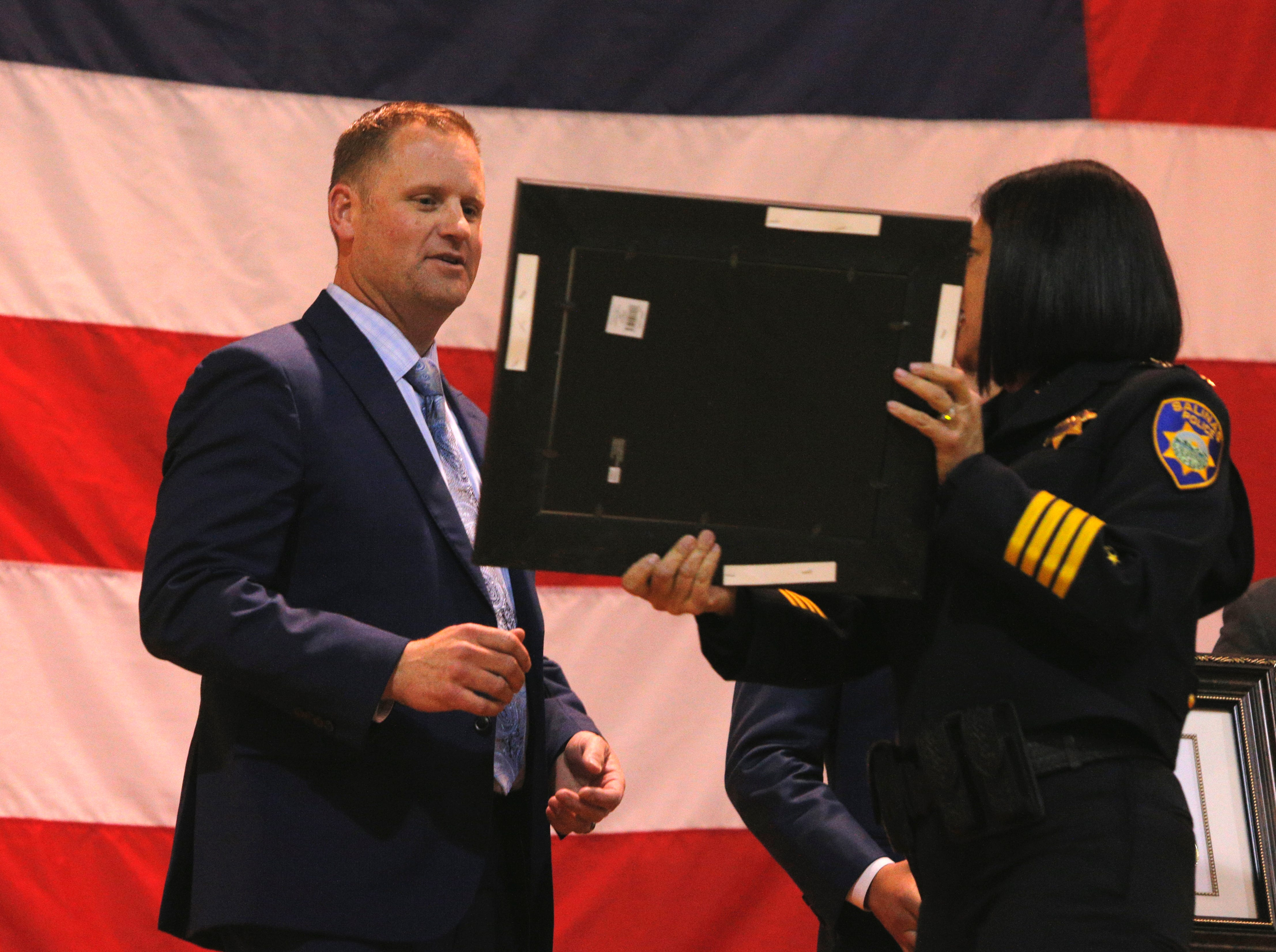 Salinas police Sgt. Dale Fors is shown a certificate honoring him with the department's medal of valor March 14, 2019, at the Salinas Police Department's 2018 awards ceremony.