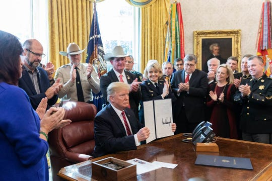 President Donald J. Trump signs the first veto of his presidency Friday, March 15, in the Oval Office of the White House to strike down legislation to halt his Executive Order declaring a National Emergency along the southern border of the United States. Wicomico County Sheriff Mike Lewis is at right.