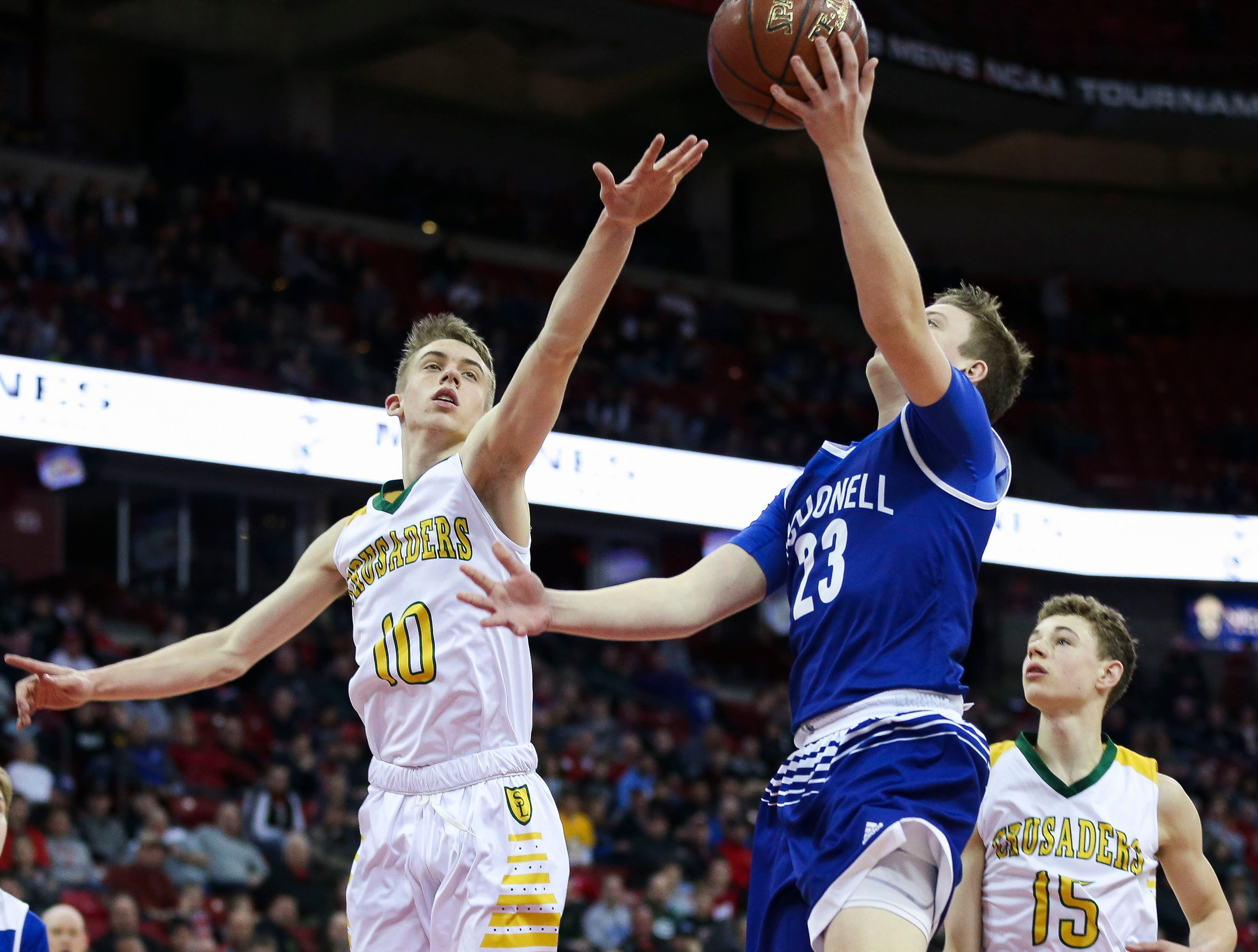 Sheboygan Lutheran High School's Graden Grabowski (10) contests a shot by McDonell Central Catholic High School's Logan Hughes (23) in a Division 5 boys basketball state semifinal on Friday, March 15, 2019, at the Kohl Center in Madison, Wis.