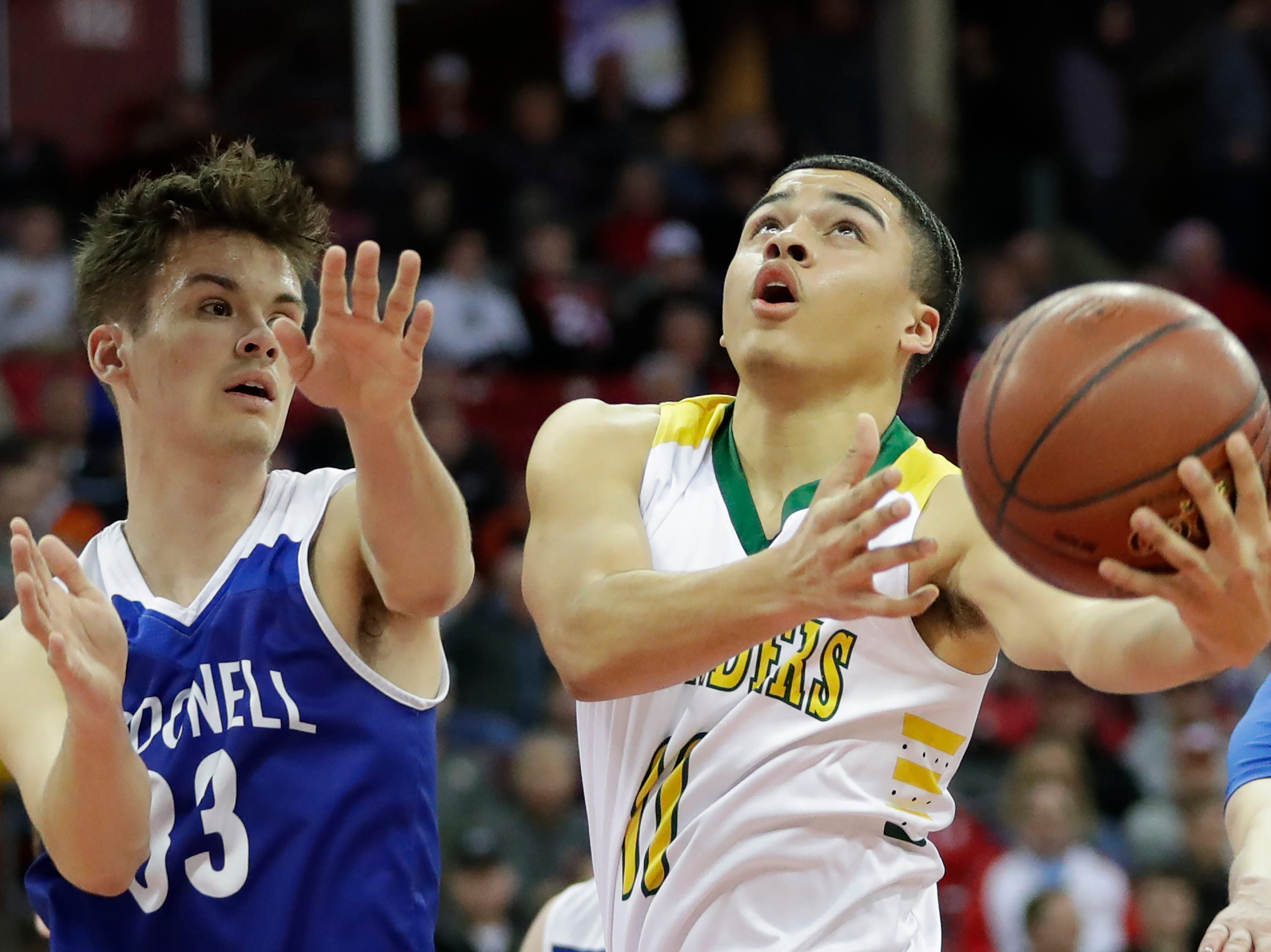 Sheboygan Area Lutheran High School's Michael Berger (11) takes it to the hoop against McDonell Central Catholic High School's Charlie Bleskachek (33) during their WIAA Division 5 boys basketball state semifinal at the Kohl Center Friday, March 15, 2019, in Madison, Wis.