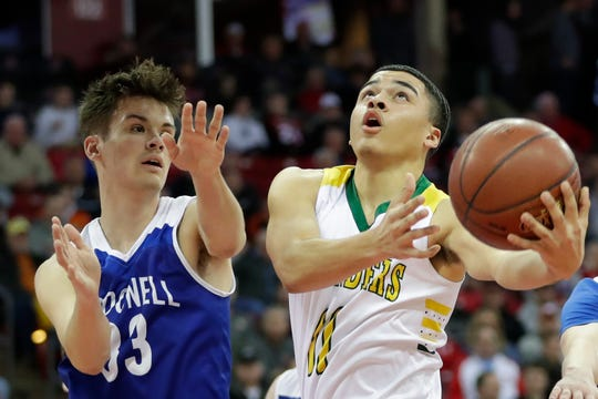 Sheboygan Lutheran's Michael Berger (11) takes it to the hoop against Chippewa Falls McDonell's Charlie Bleskachek (33) during a WIAA Division 5 boys basketball state semifinal Friday at the Kohl Center in Madison.