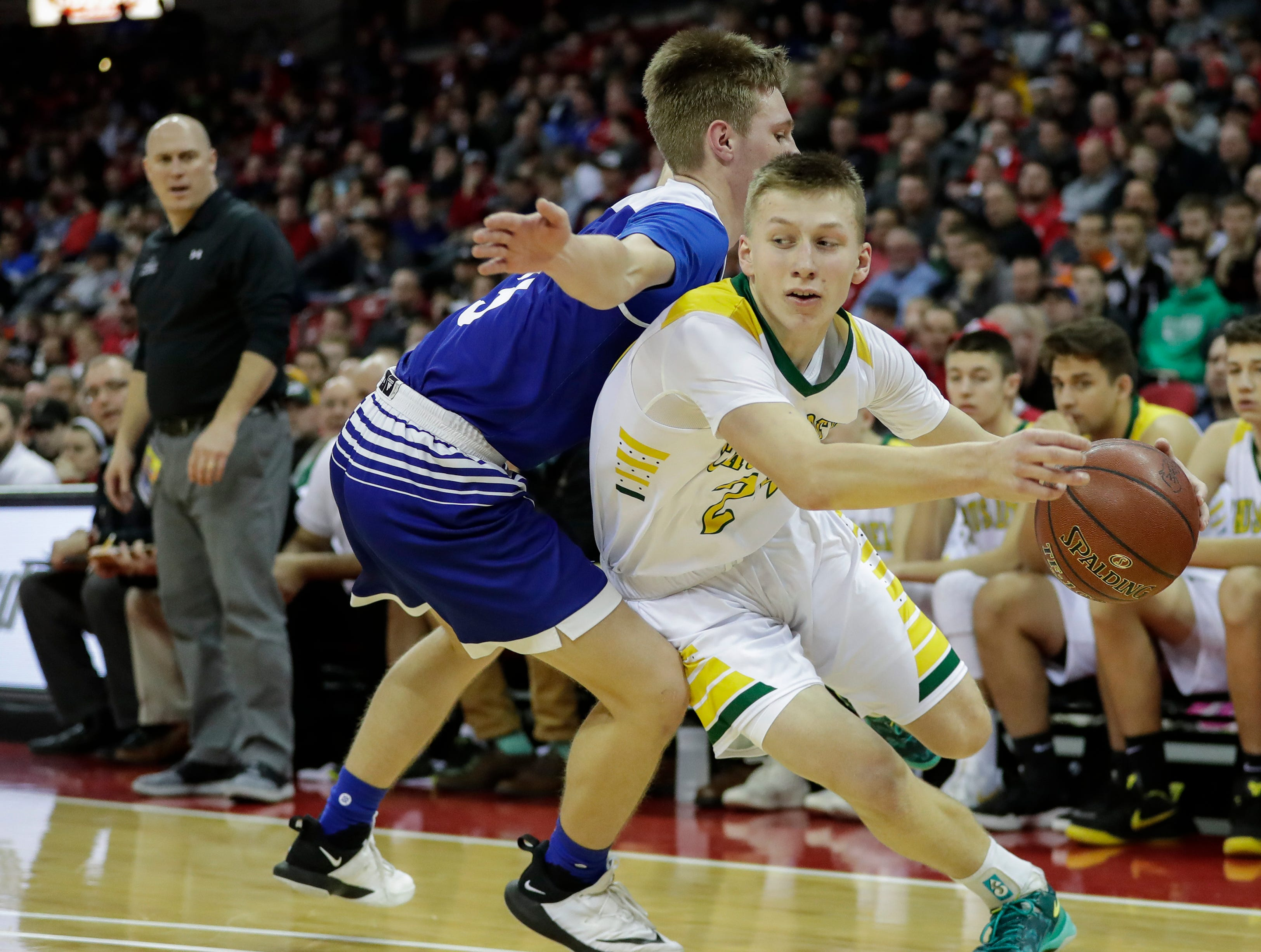 Sheboygan Area Lutheran High School's Casey Verhagen (24) drives down the baseline against McDonell Central Catholic High School's JD Bohaty (3) during their WIAA Division 5 boys basketball state semifinal at the Kohl Center Friday, March 15, 2019, in Madison, Wis.
