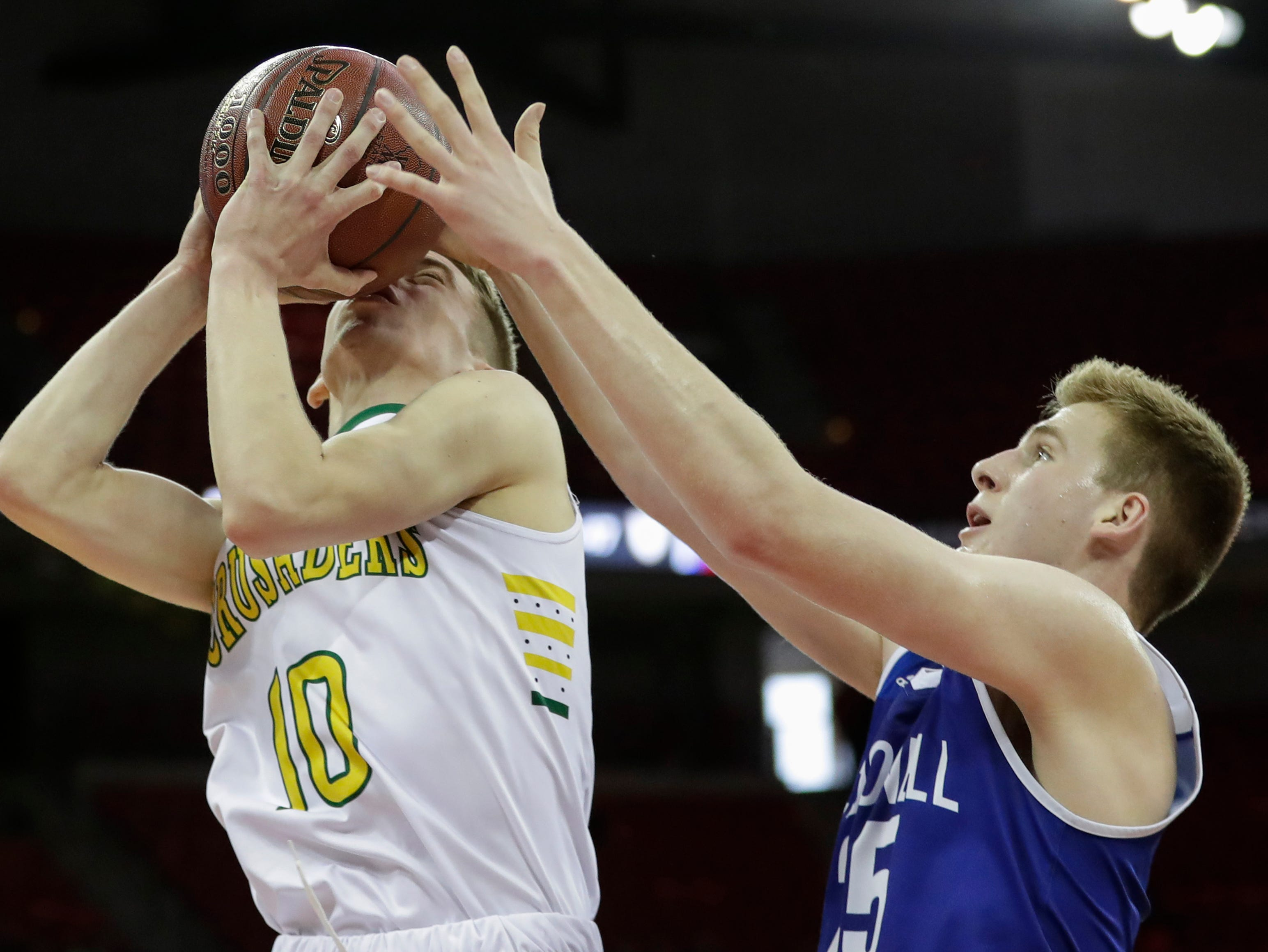 Sheboygan Area Lutheran High School's Graden Grabowski (10) is fouled as he goes up for a shot against McDonell Central Catholic High School's Eion Kressin (25) during their WIAA Division 5 boys basketball state semifinal at the Kohl Center Friday, March 15, 2019, in Madison, Wis.
