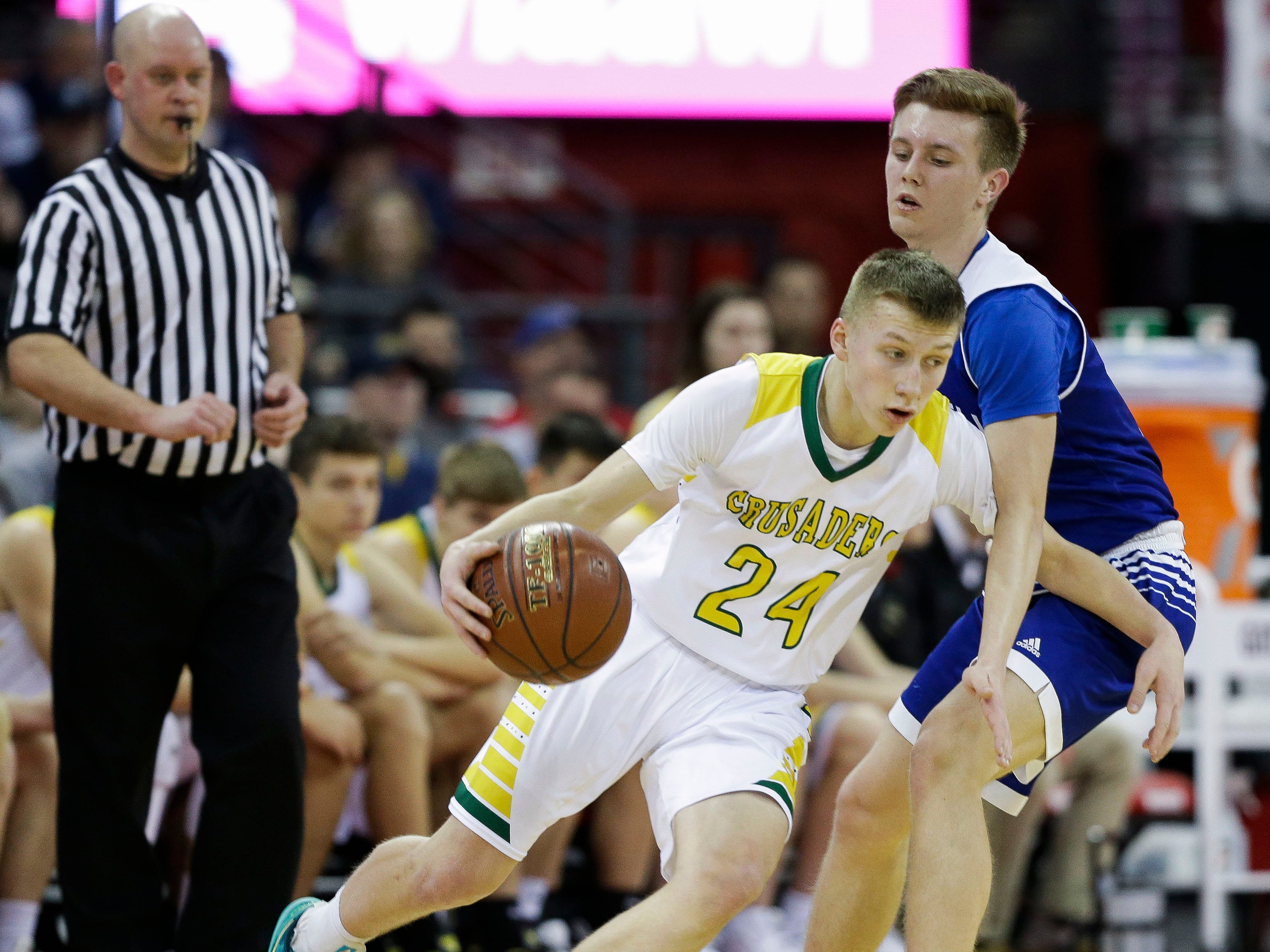 Sheboygan Lutheran High School's Casey Verhagen (24) tries to dribble past McDonell Central Catholic High School's Jaebin Bourget (5) in a Division 5 boys basketball state semifinal on Friday, March 15, 2019, at the Kohl Center in Madison, Wis.