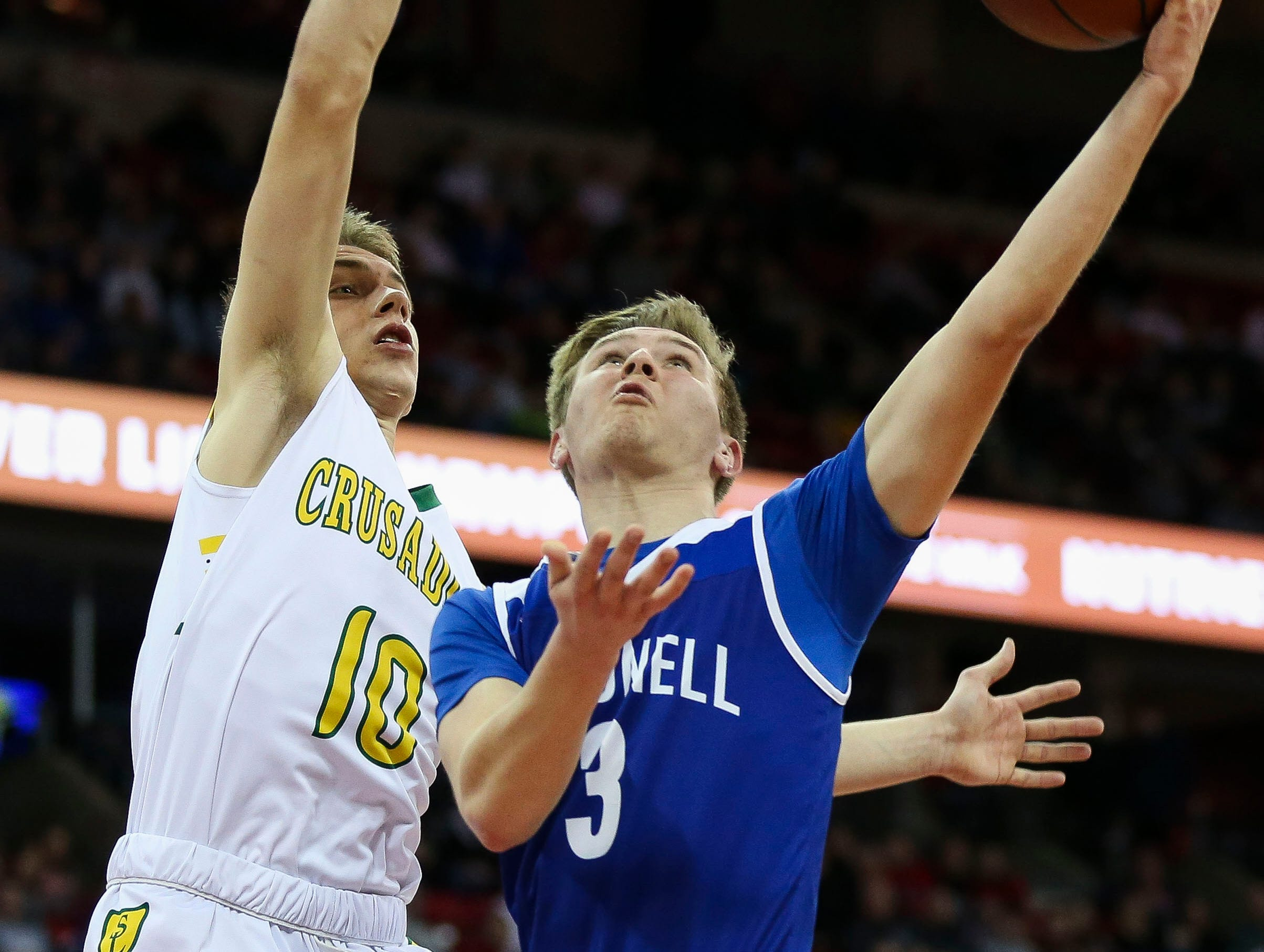 Sheboygan Lutheran High School's Graden Grabowski (10) contests a shot by McDonell Central Catholic High School's JD Bohaty (3) in a Division 5 boys basketball state semifinal on Friday, March 15, 2019, at the Kohl Center in Madison, Wis.