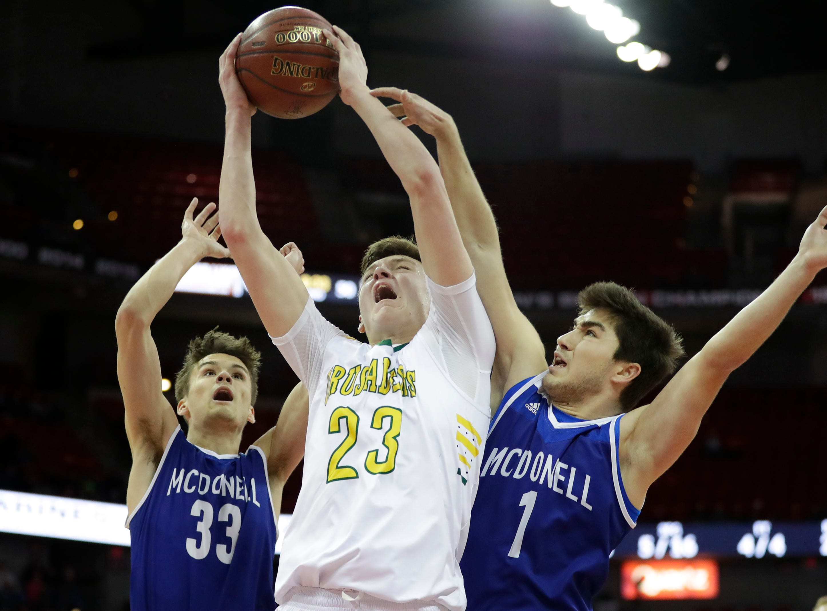 Sheboygan Area Lutheran High School's Jacob Ognacevic (23) is fouled as he looks to shoot against McDonell Central Catholic High School during their WIAA Division 5 boys basketball state semifinal at the Kohl Center Friday, March 15, 2019, in Madison, Wis.