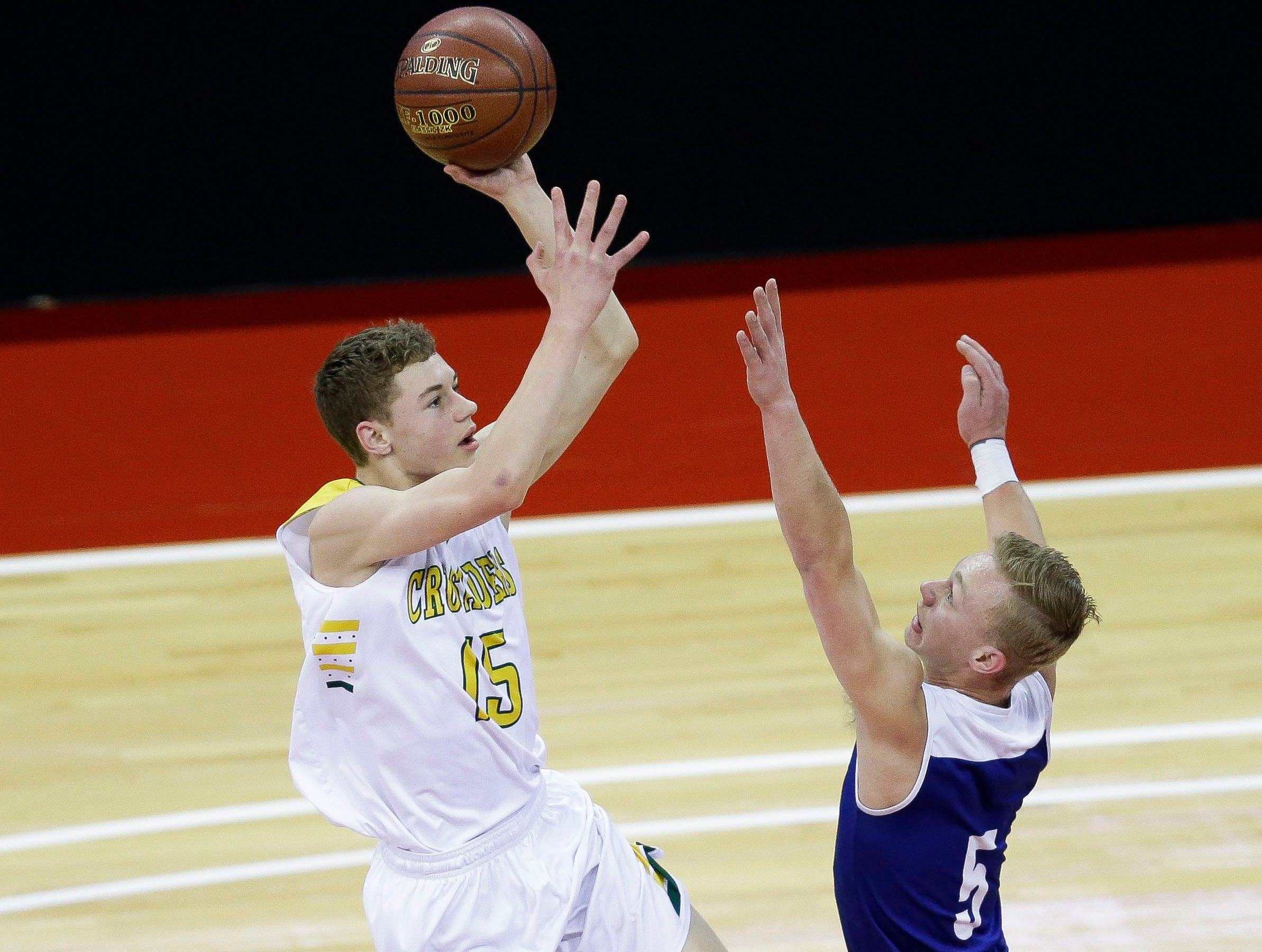 Sheboygan Lutheran High School's Delvin Barnstable (15) puts up a shot over McDonell Central Catholic High School's Jaebin Bourget (5) in a Division 5 boys basketball state semifinal on Friday, March 15, 2019, at the Kohl Center in Madison, Wis.