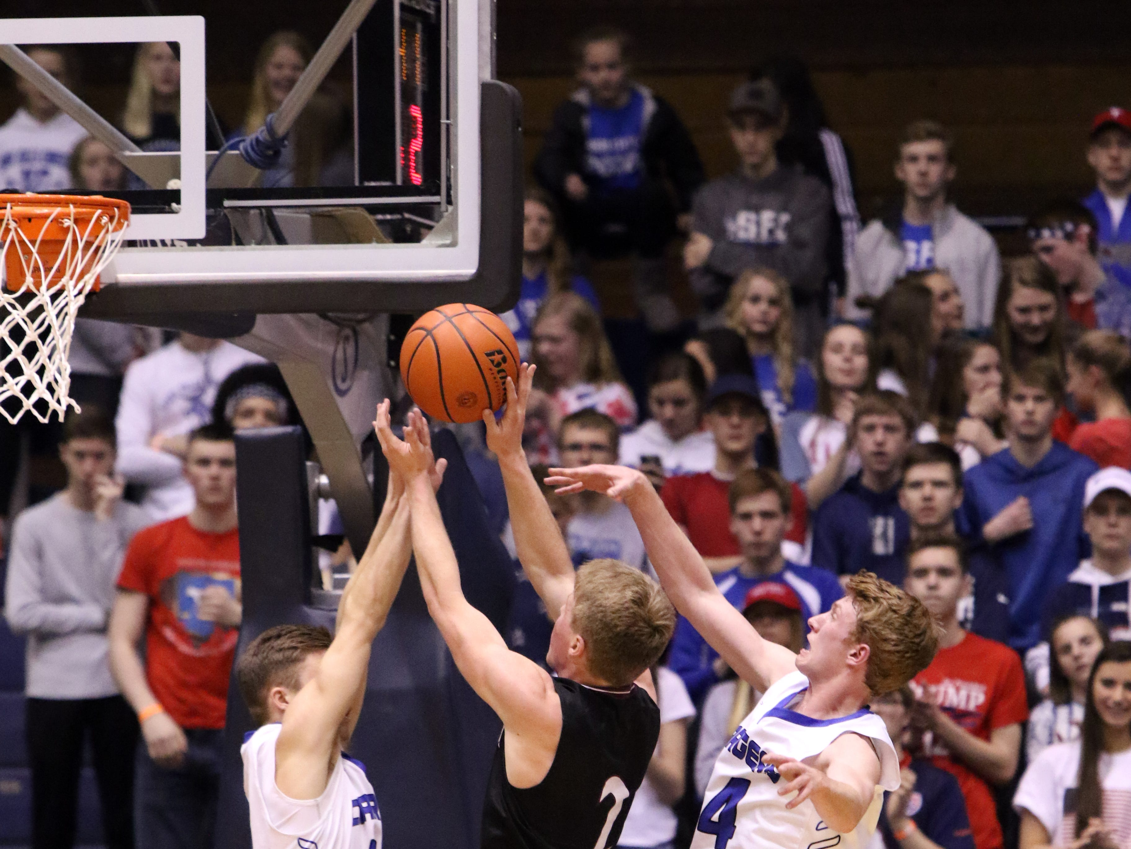 Dawson Mulder (L) and Gavin Schipper of Sioux Falls Christian attempt to block the shot by Caileb Reilly of Madison during Thursday's game at the Arena.