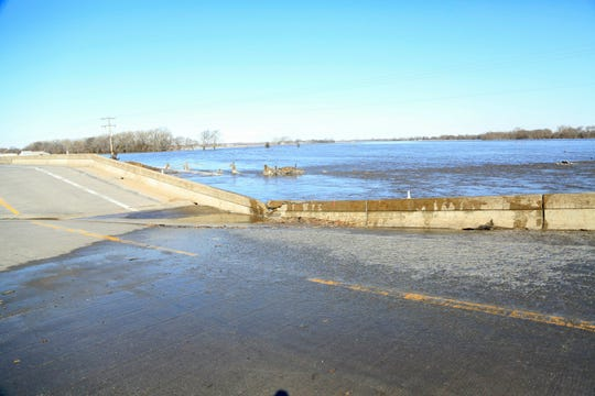 A bridge brought down by flood waters is seen near Norfolk, Neb., Friday, March 15, 2019. Thousands of people have been urged to evacuate along eastern Nebraska rivers as a massive late-winter storm has pushed streams and rivers out of their banks throughout the Midwest.