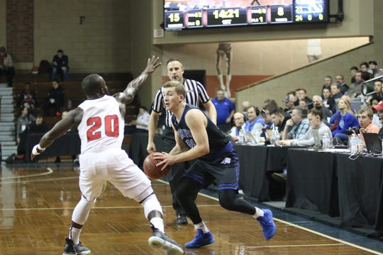 DWU's Ty Hoglund dealt with the pesky defense of Indiana Wesleyan's Joel Okafor in the Round of 16 at the NAIA tournament.