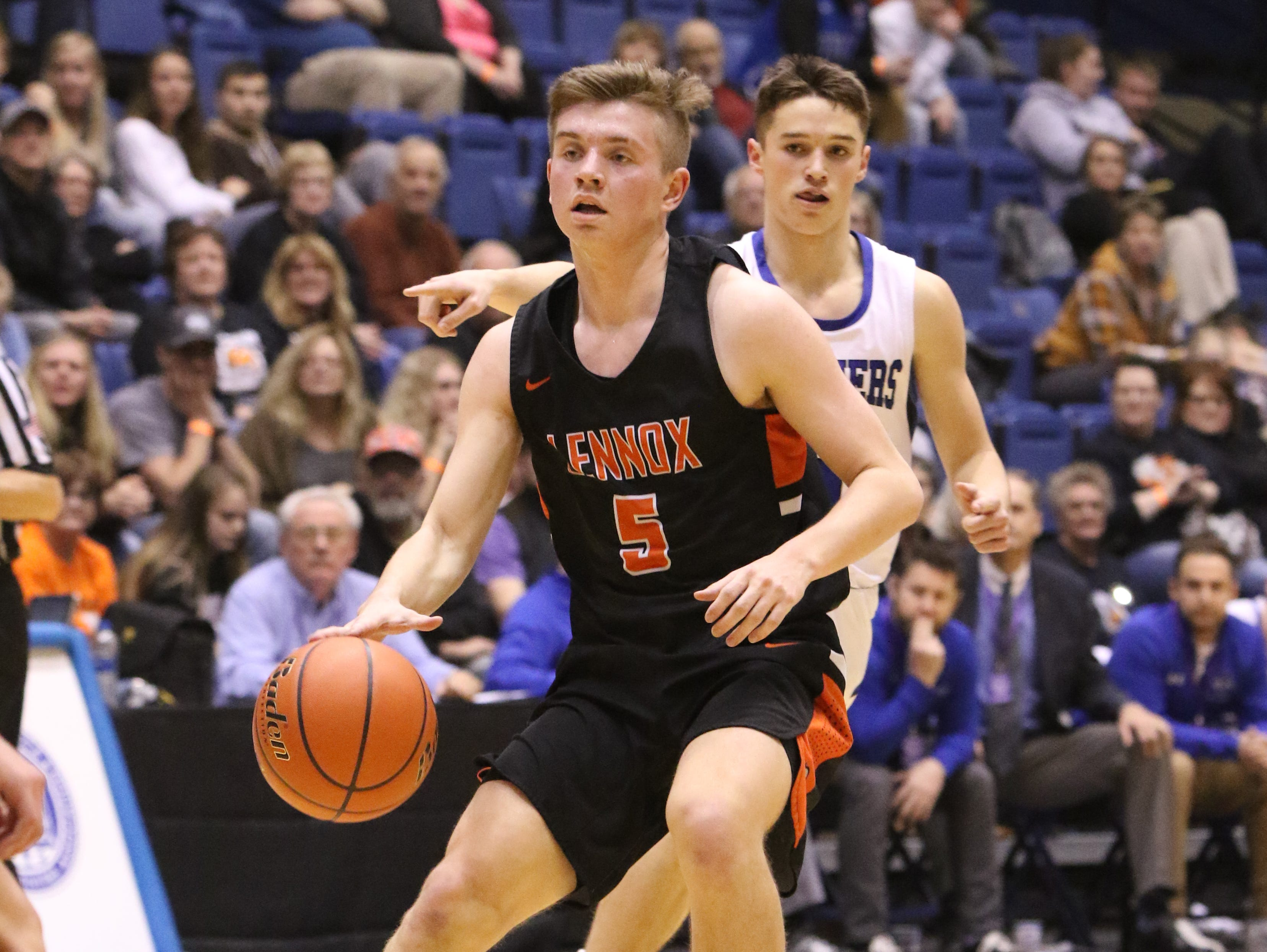 Josh Arlt of Lennox dribbles ahead of Michael Gylten of St Thomas More during Thursday night's game at the Arena in Sioux Falls.