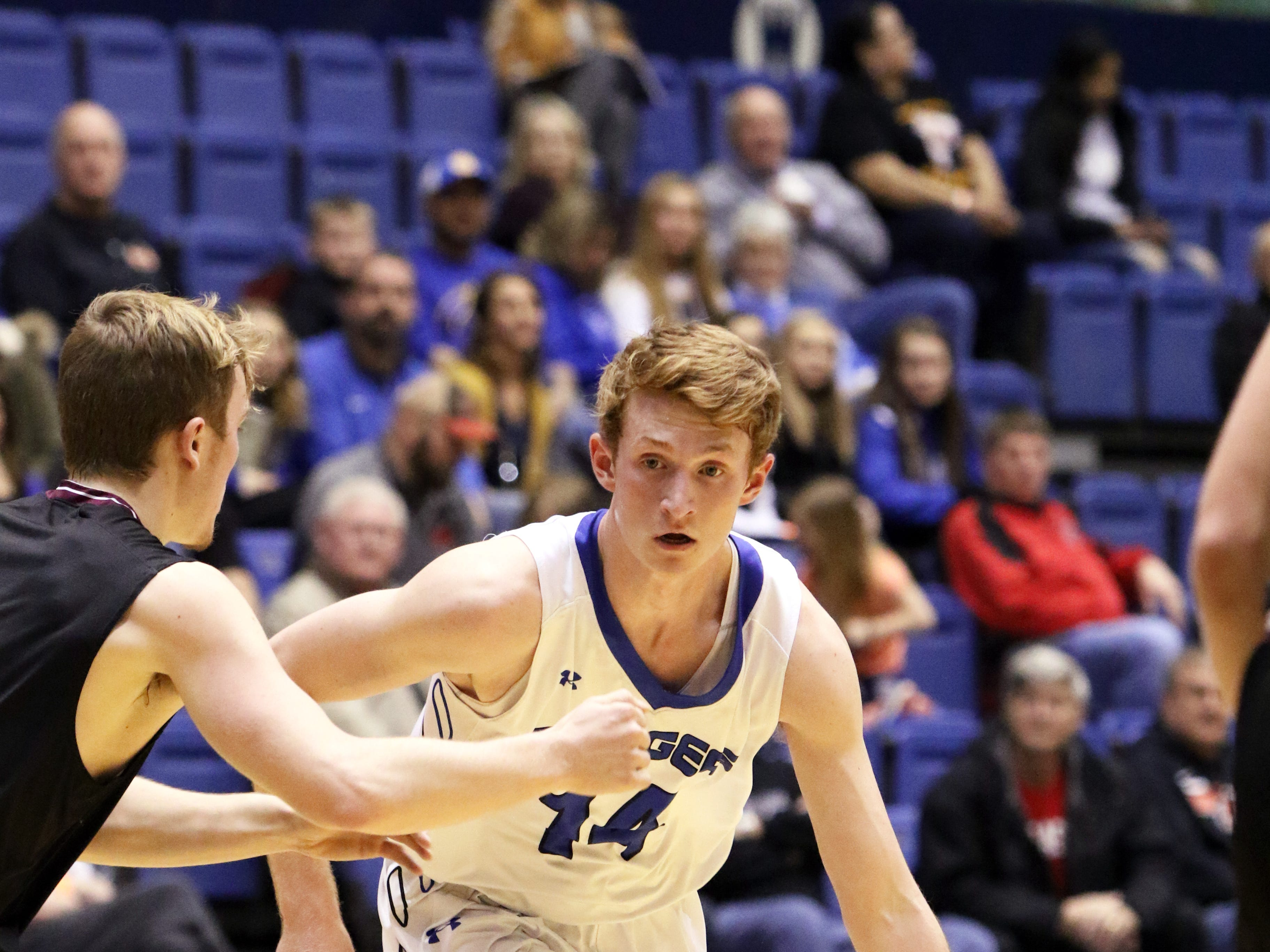 Gavin Schipper of Sioux Falls Christian looks to get around Nic Comes of Madison during Thursday's game at the Arena in Sioux Falls.