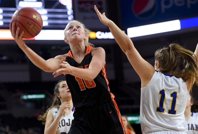 The Orioles' Madysen Vlastuin scoops a shot past her Trojan defender during their semifinal game at the State A Girls Basketball Tourney on Friday in Sioux Falls.