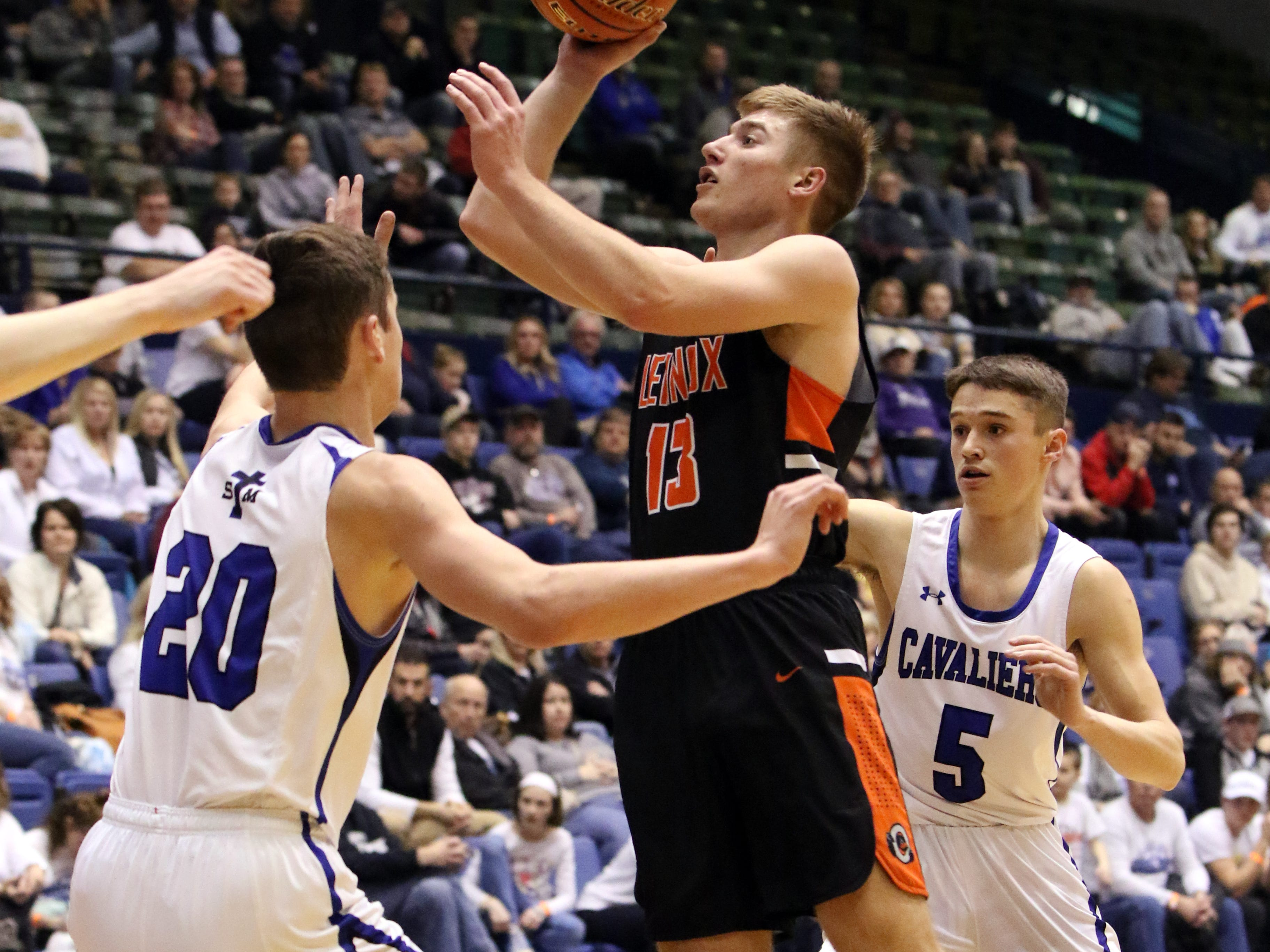 Quincy Ihnen of Lennox shoots the ball between Connor Hollenbeck (20) and Michael Gylten of St Thomas More during Thursday's game at the Arena.