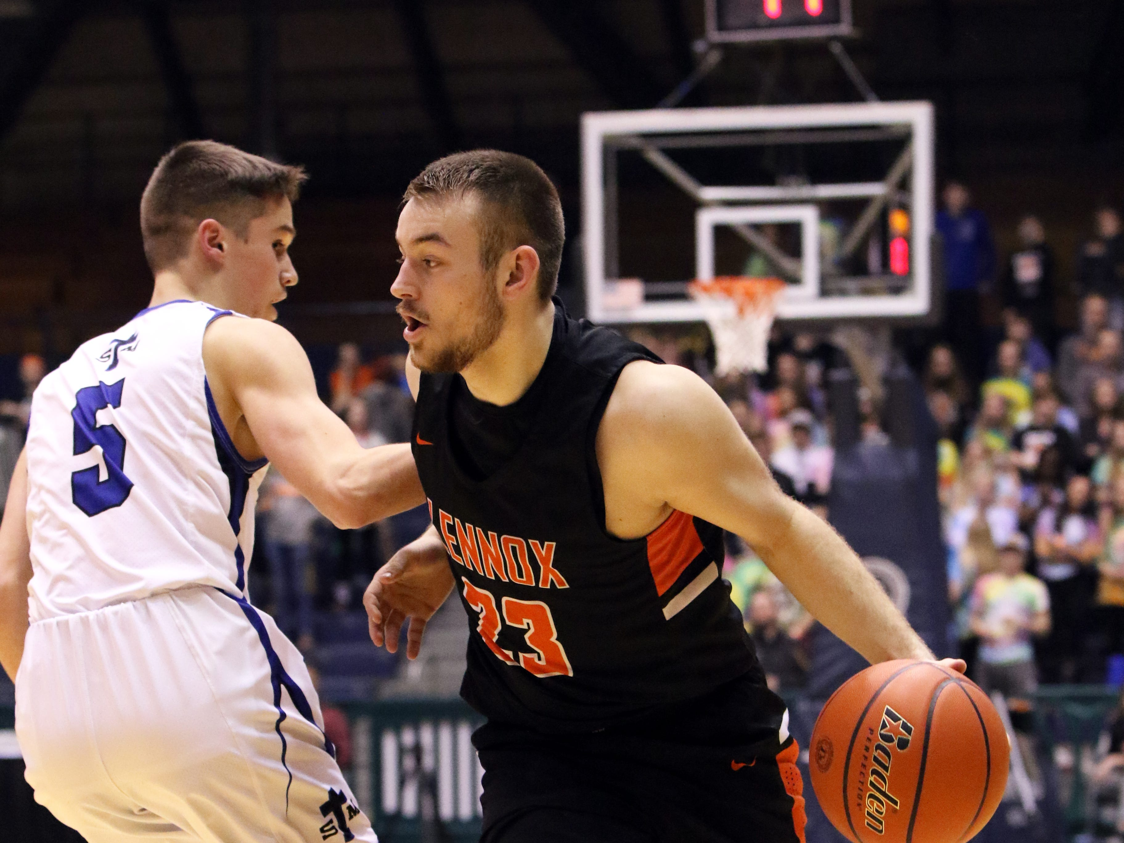 Will Daugherty of Lennox goes around the defense by Michael Gylten of St Thomas More during Thursday night's game at the Arena in Sioux Falls.