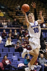 Mitchell Oostra of Sioux Falls Christian lays in a shot ahead of Madison's Doyle Brown during Thursday's game at the Arena in Sioux Falls.