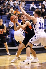 Zach Leisinger of Lennox getsw pressure from Ryan Wojcik of St Thomas More during Thursday night's game at the Arena in Sioux Falls.